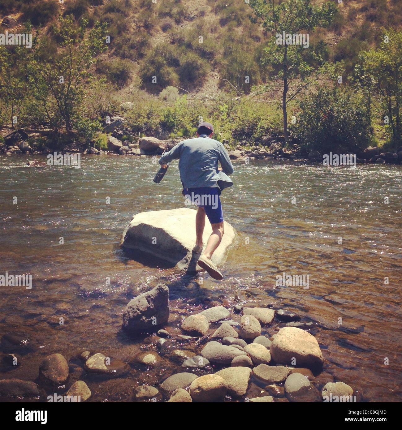 Uomo di saltare attraverso le rocce nel fiume Immagini Stock
