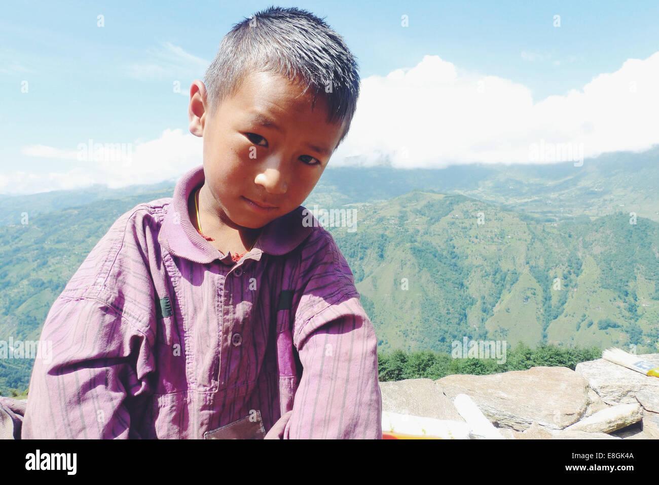 Il Nepal, ritratto del ragazzo (10-11) seduto sul muro di pietra in montagna Immagini Stock