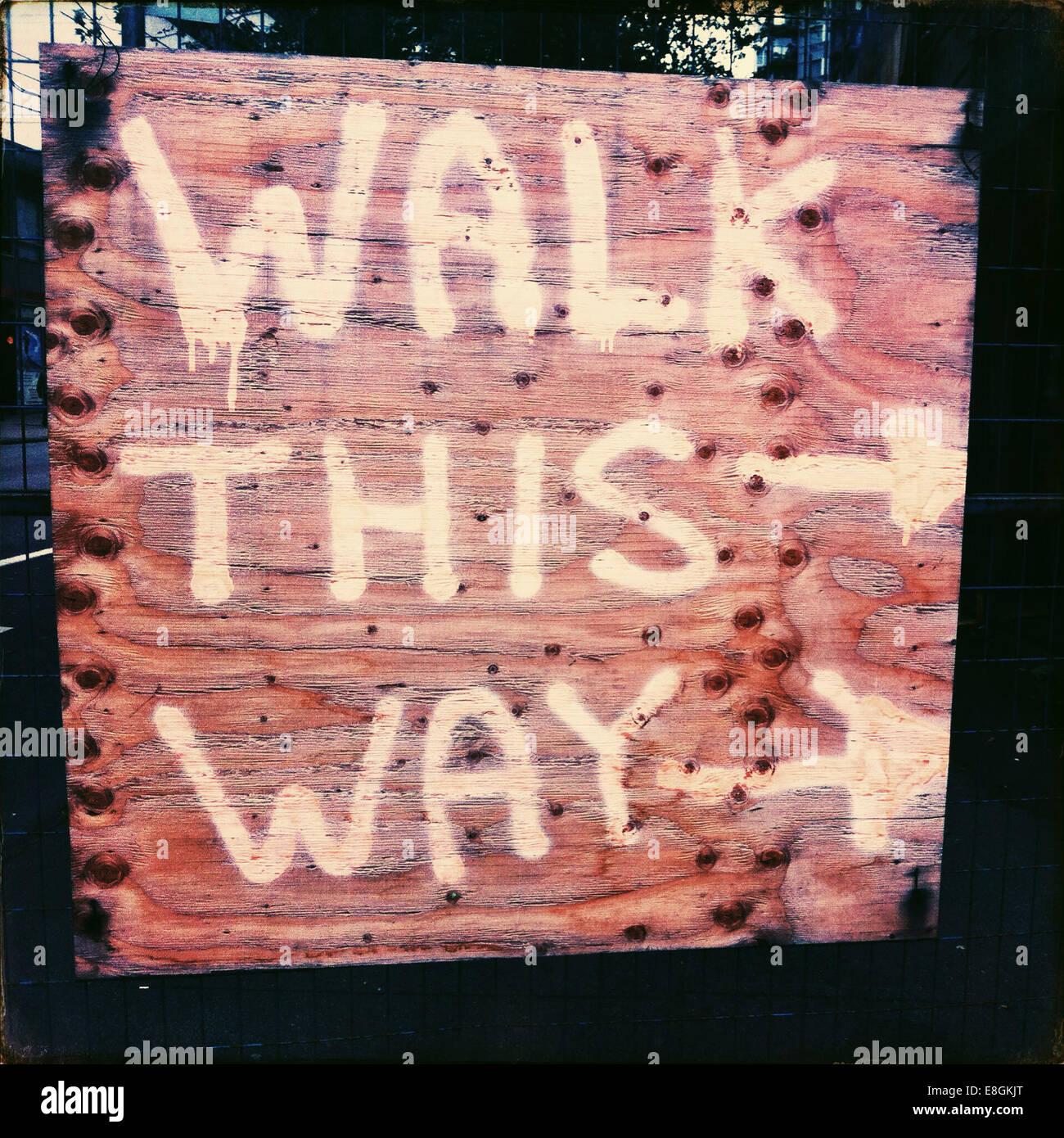 A piedi in questo modo segno di direzione sul marciapiede vicino al sito in costruzione Immagini Stock