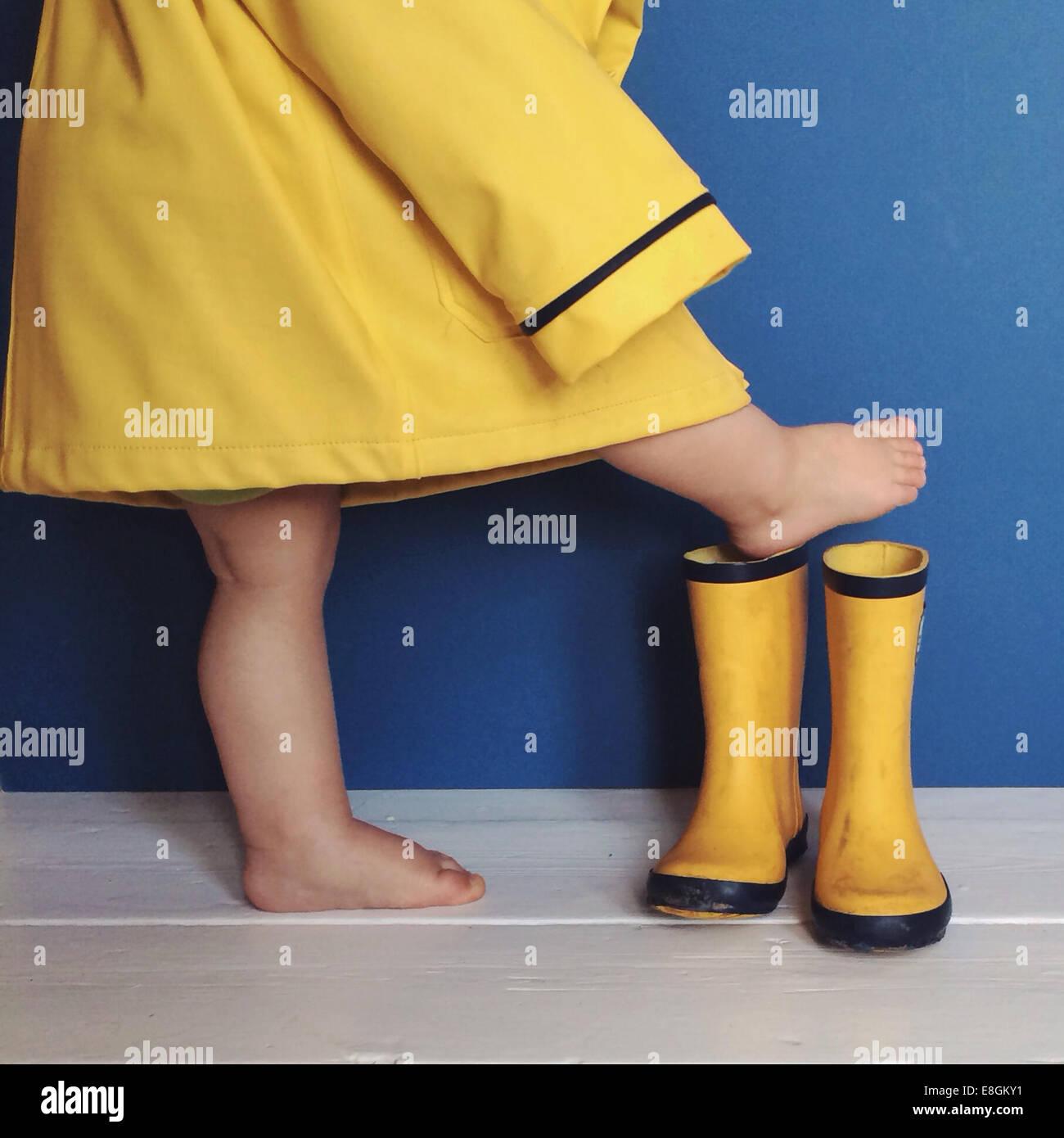 Ragazzo in impermeabile a mettere su gli stivali da pioggia Immagini Stock
