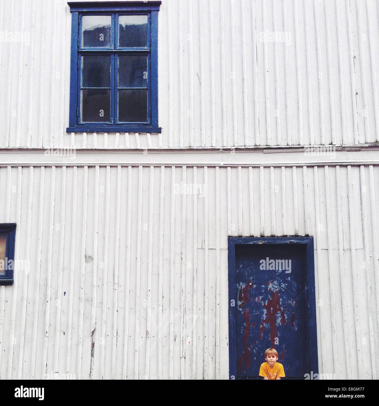Norvegia, Fredrikstad, ragazzo (10-11) seduti contro house Immagini Stock