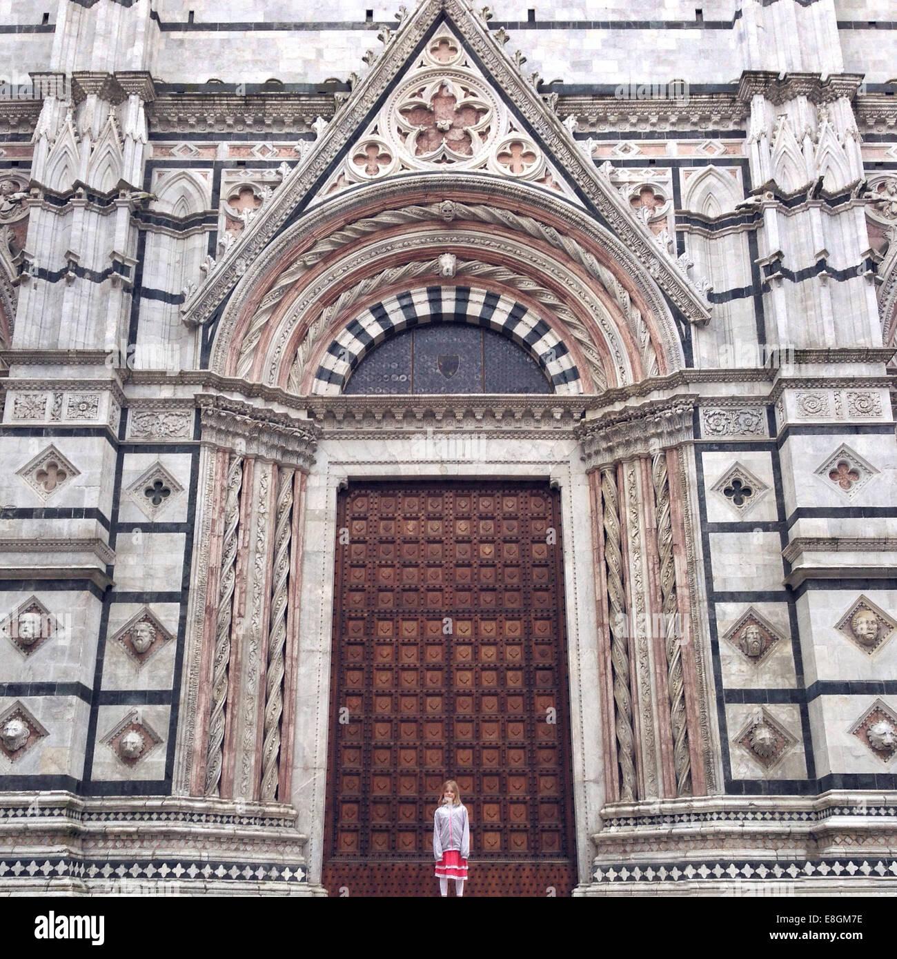 Italia, Toscana, Siena, ragazza (12-13) in piedi di fronte cattedrale Immagini Stock