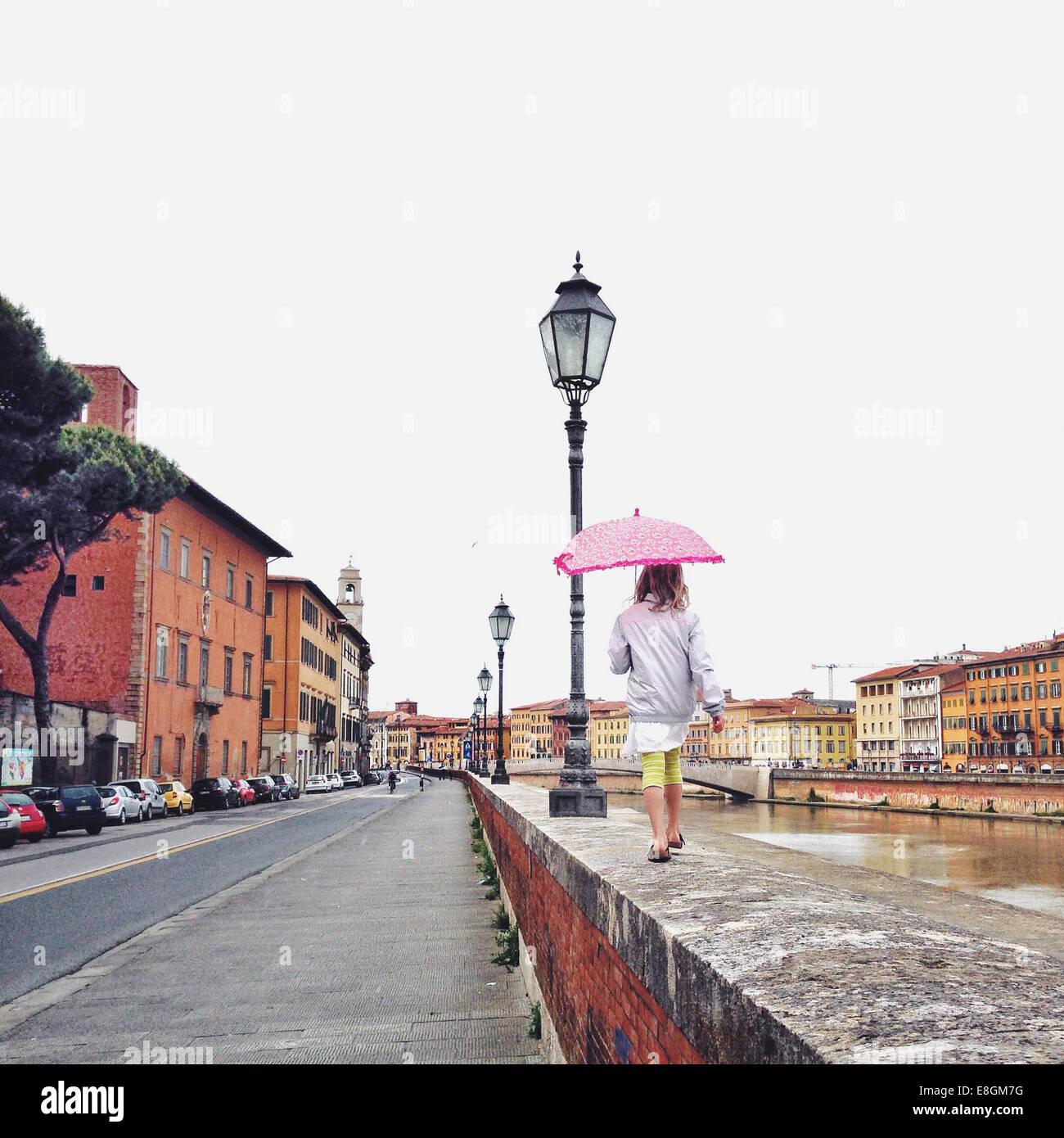 L'Italia, Toscana, Pisa, ragazza (12-13) con ombrellone camminando sulla mensola Immagini Stock