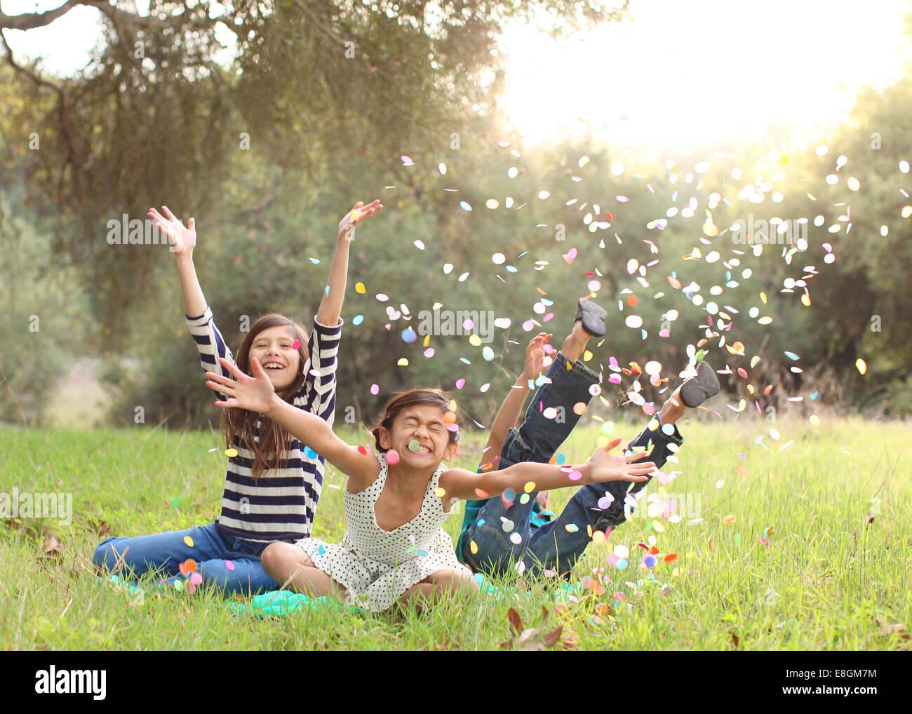 Tre bambini seduti nel parco gettando coriandoli in aria Immagini Stock