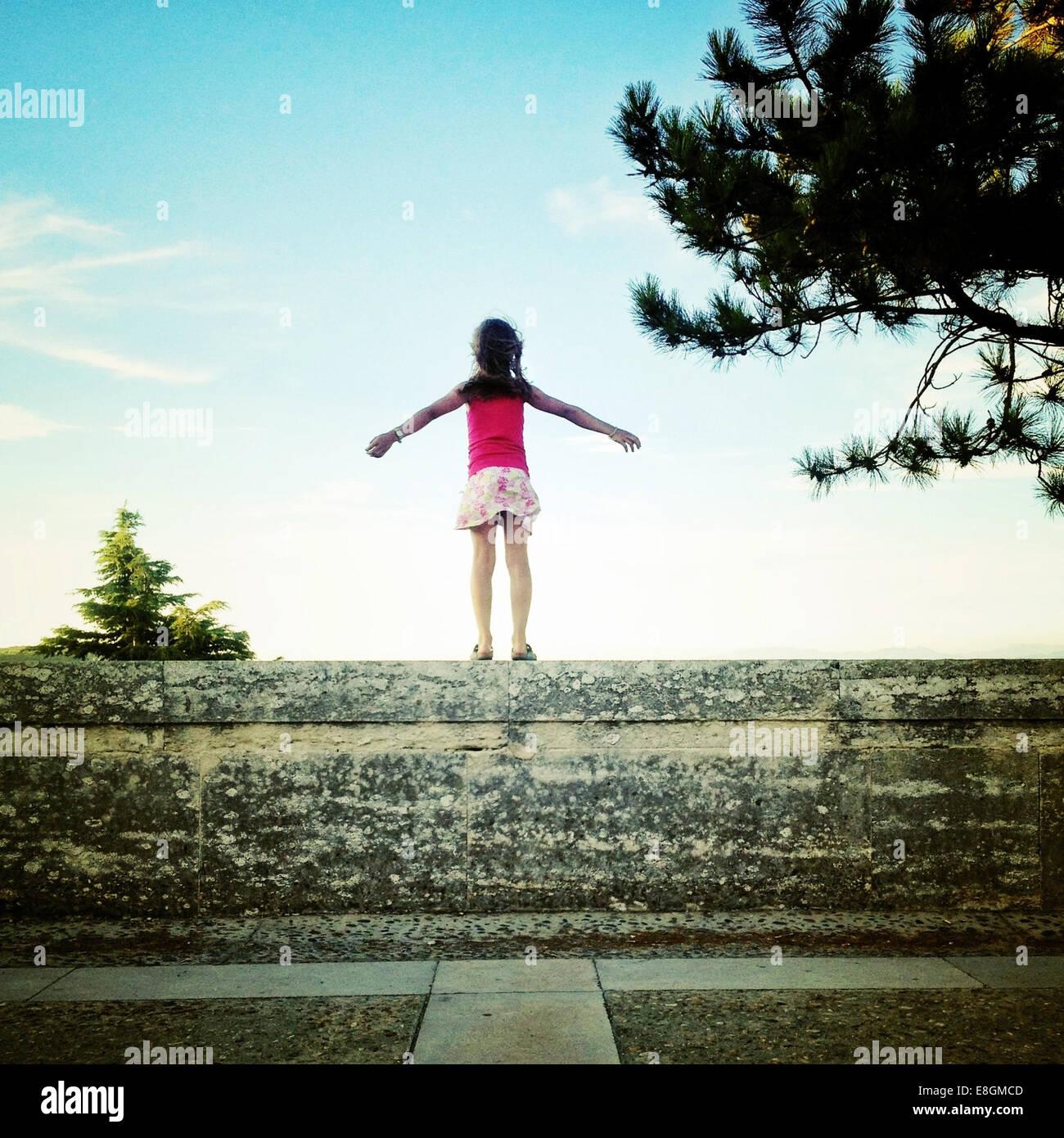 Vista posteriore di una ragazza in piedi sulla parete Immagini Stock