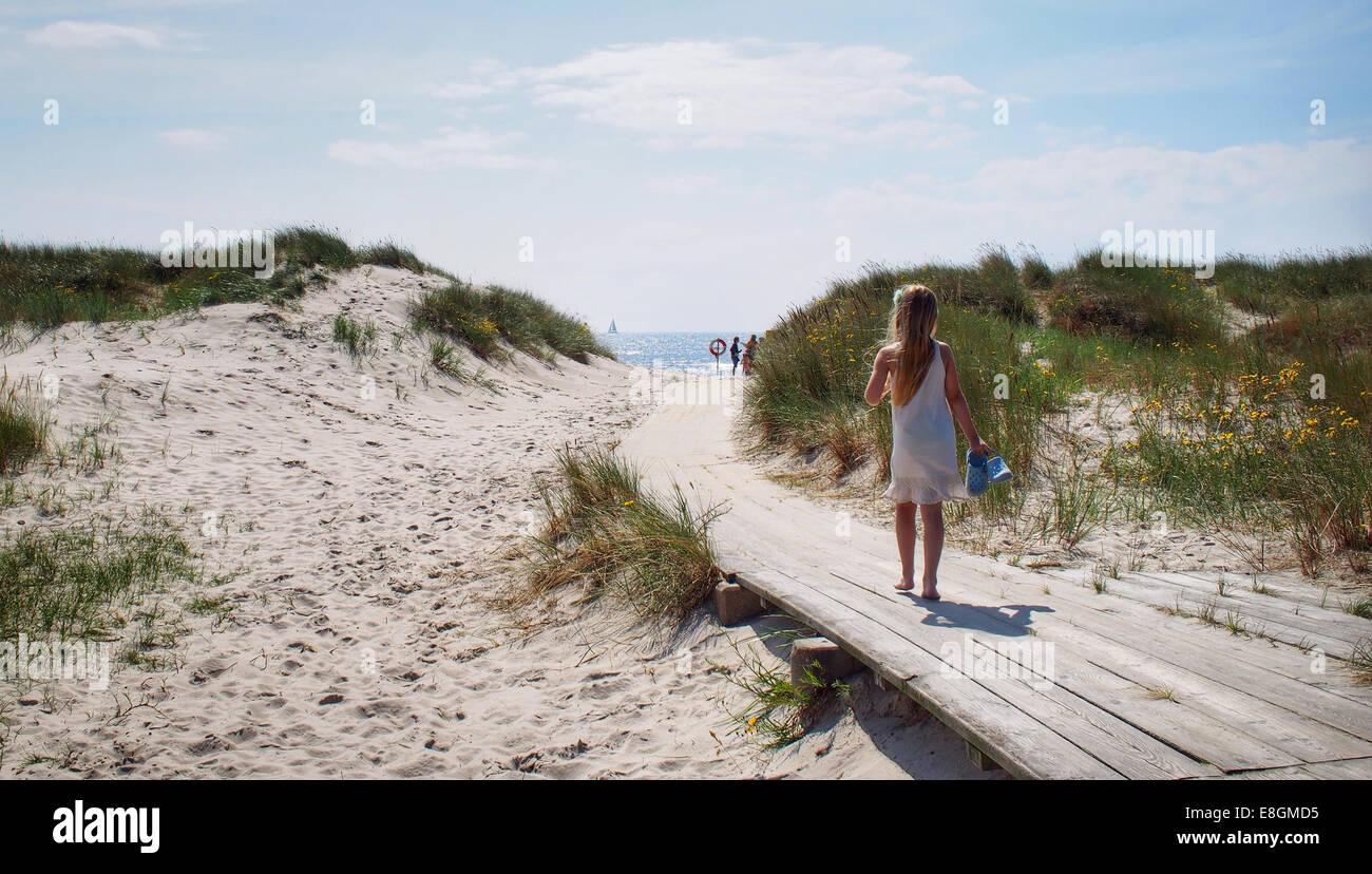 La Svezia, giovane ragazza (8-9 anni) camminando sul percorso di legno verso il mare Immagini Stock