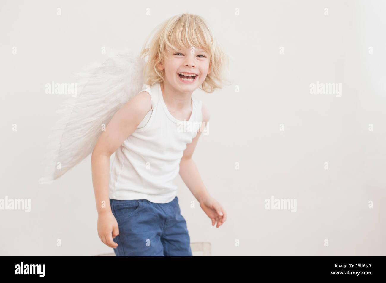 Ritratto di ridere ragazzino con ali ad angolo Immagini Stock