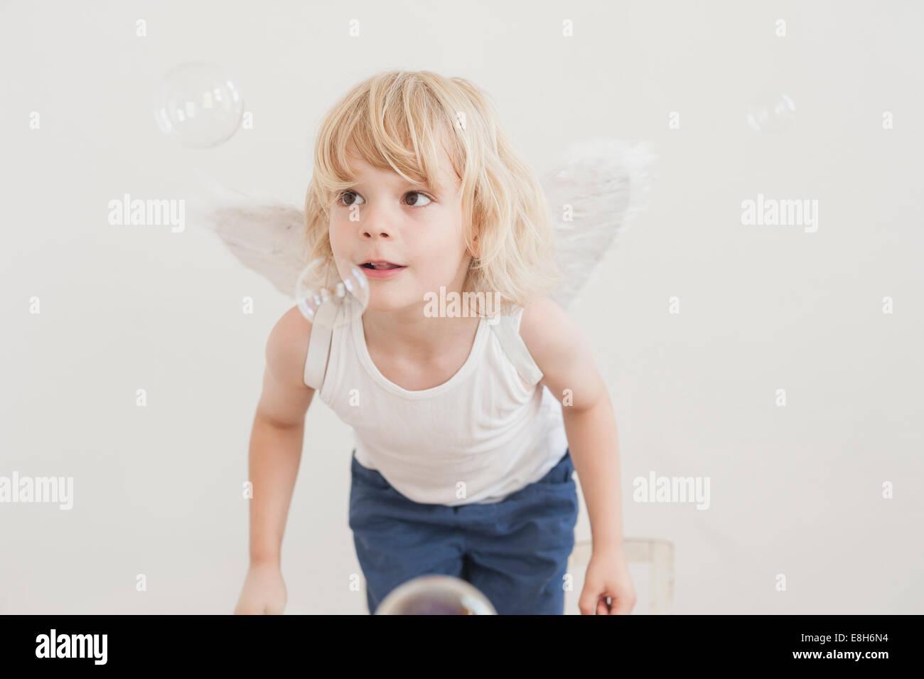Ritratto di Little Boy con angolo ali guardando le bolle di sapone Immagini Stock
