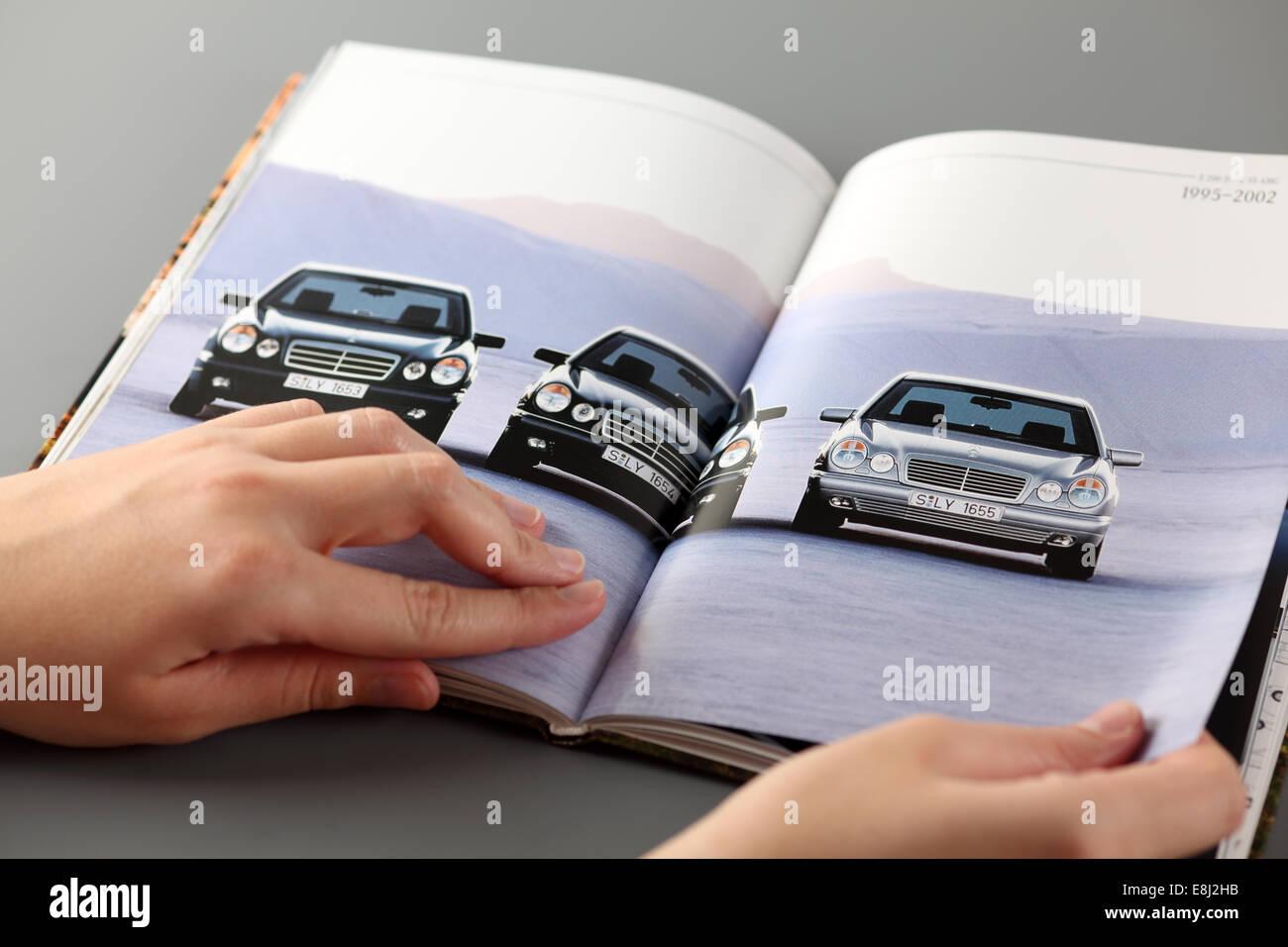 Tambov, Federazione Russa - 3 Novembre 2012: Donna esplora un catalogo di una Mercedes-Benz Cars concessionaria. Immagini Stock