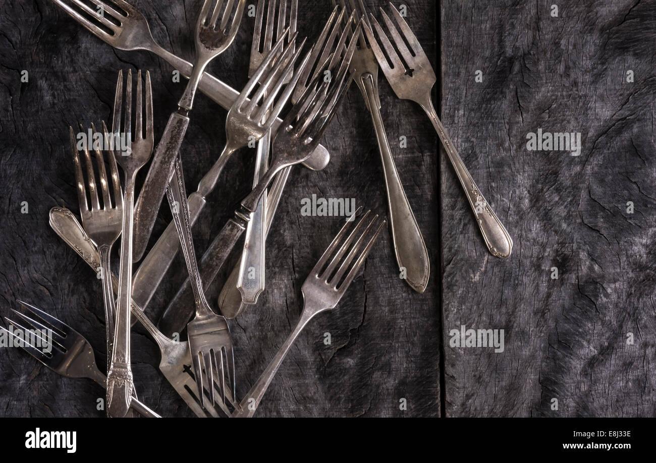 Un array di forcelle di antichi sparsi su un rustico in legno grigio superficie. Immagini Stock