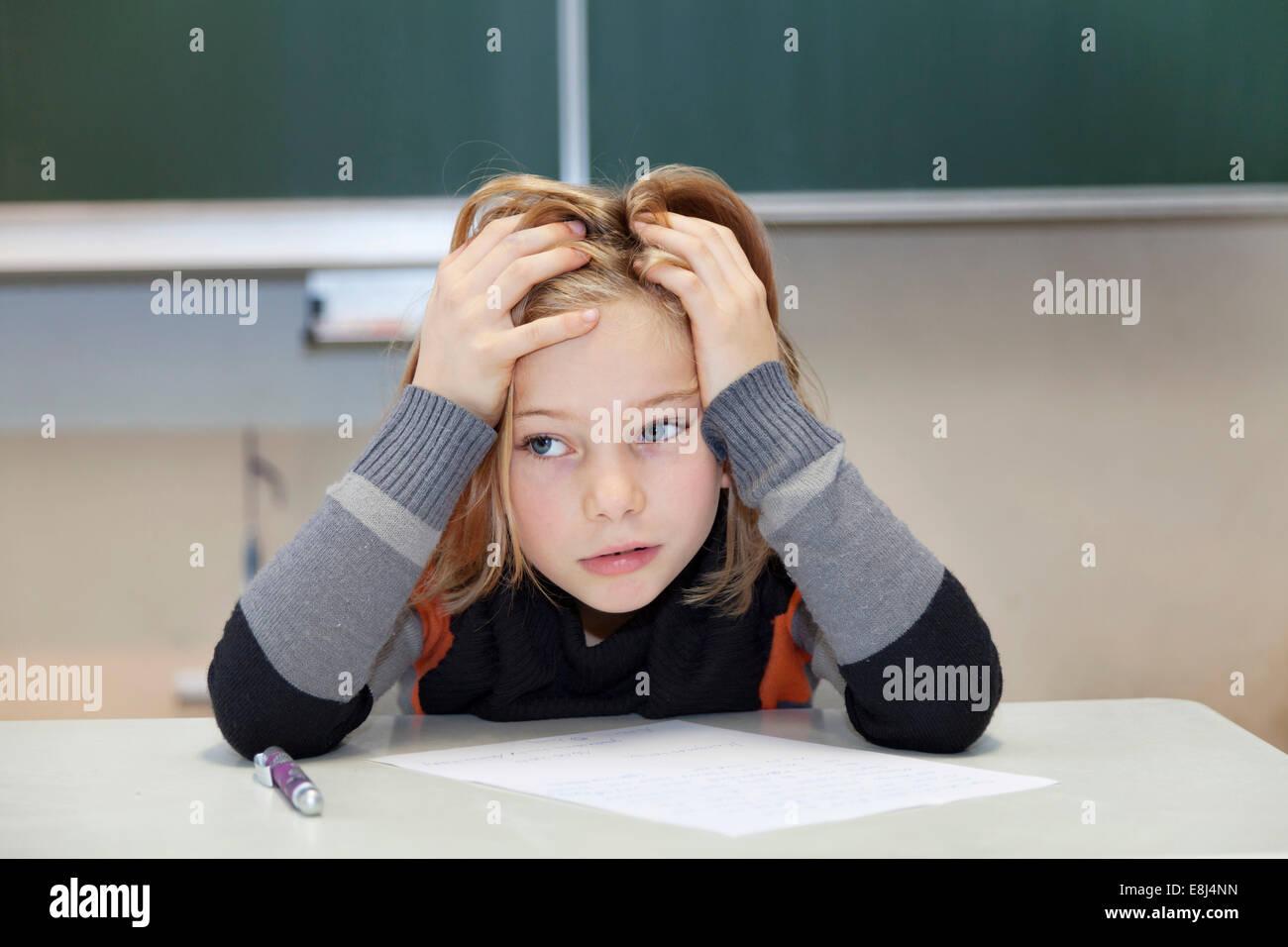 La scolaretta, 9 anni, lottando durante un esame difficile Foto Stock