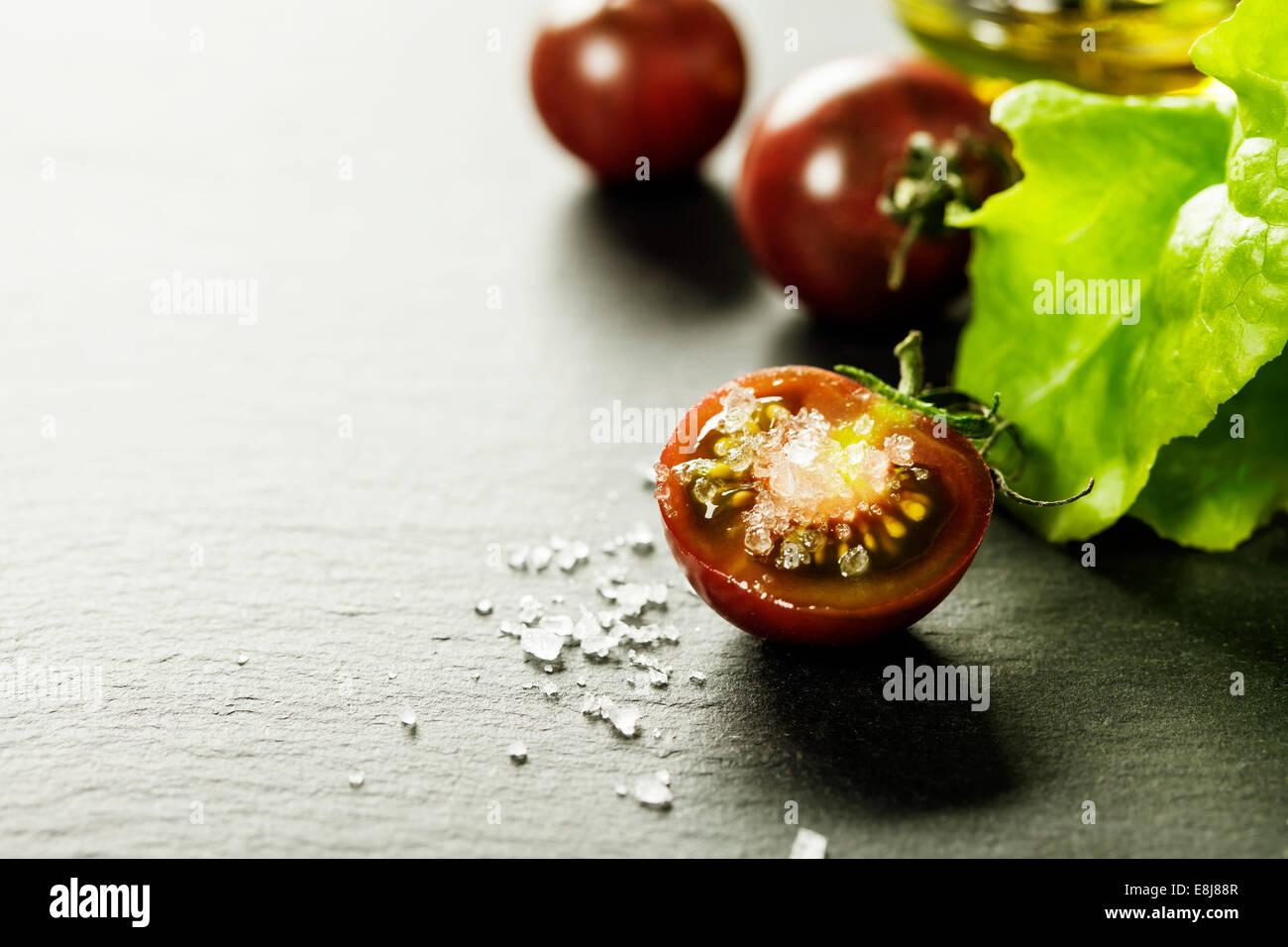 Mosti di uve fresche pomodori con foglie di insalata e sale per l'uso come ingredienti di cottura con pomodoro Immagini Stock