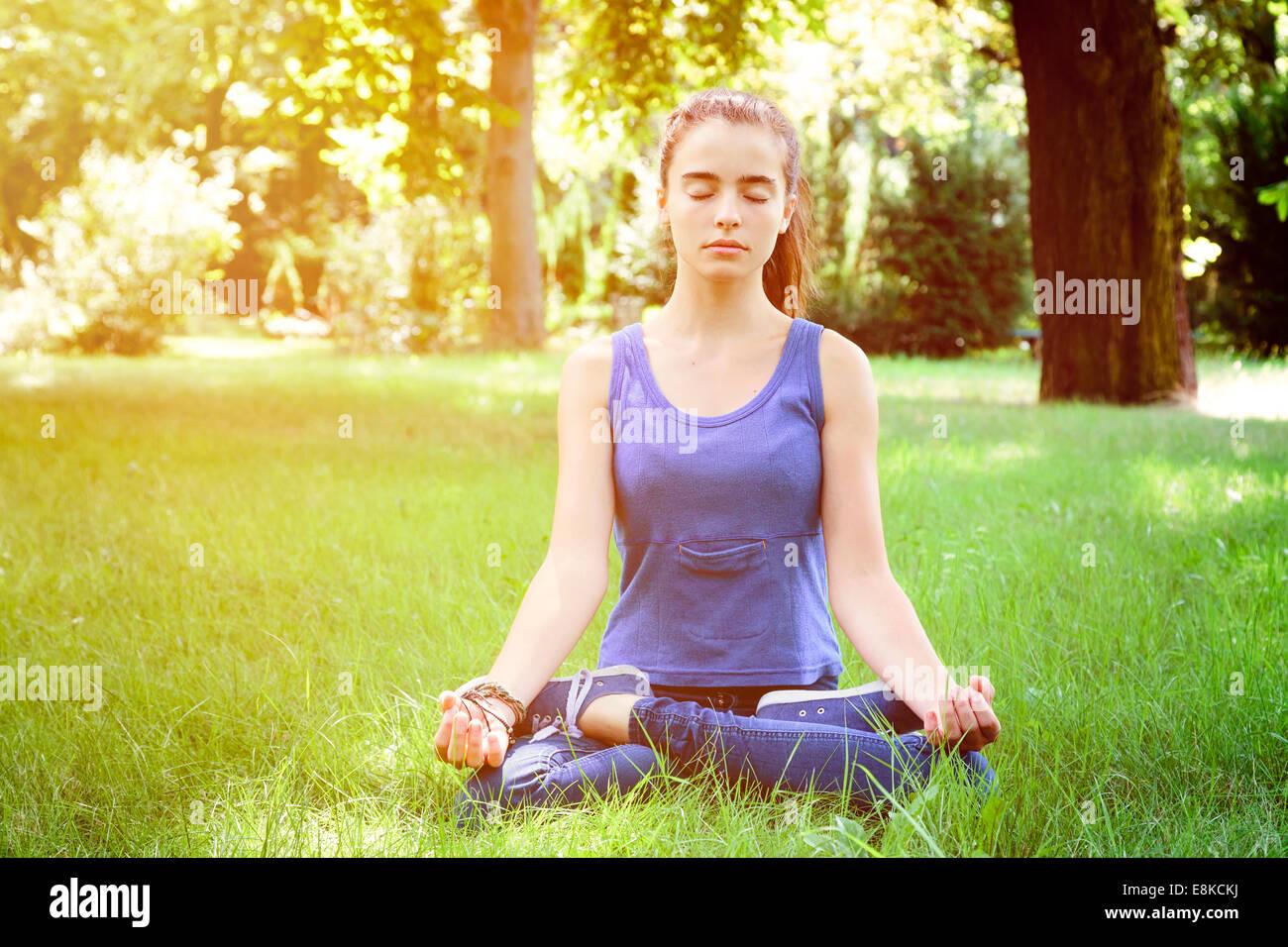 Bella ragazza adolescente medita in natura Immagini Stock