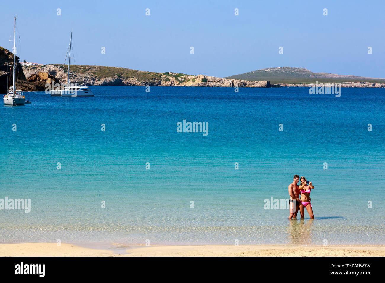 L uomo e la donna in vacanza prendendo un 'selfie' fotografia mentre in piedi sul mare di Arenal d'en Immagini Stock