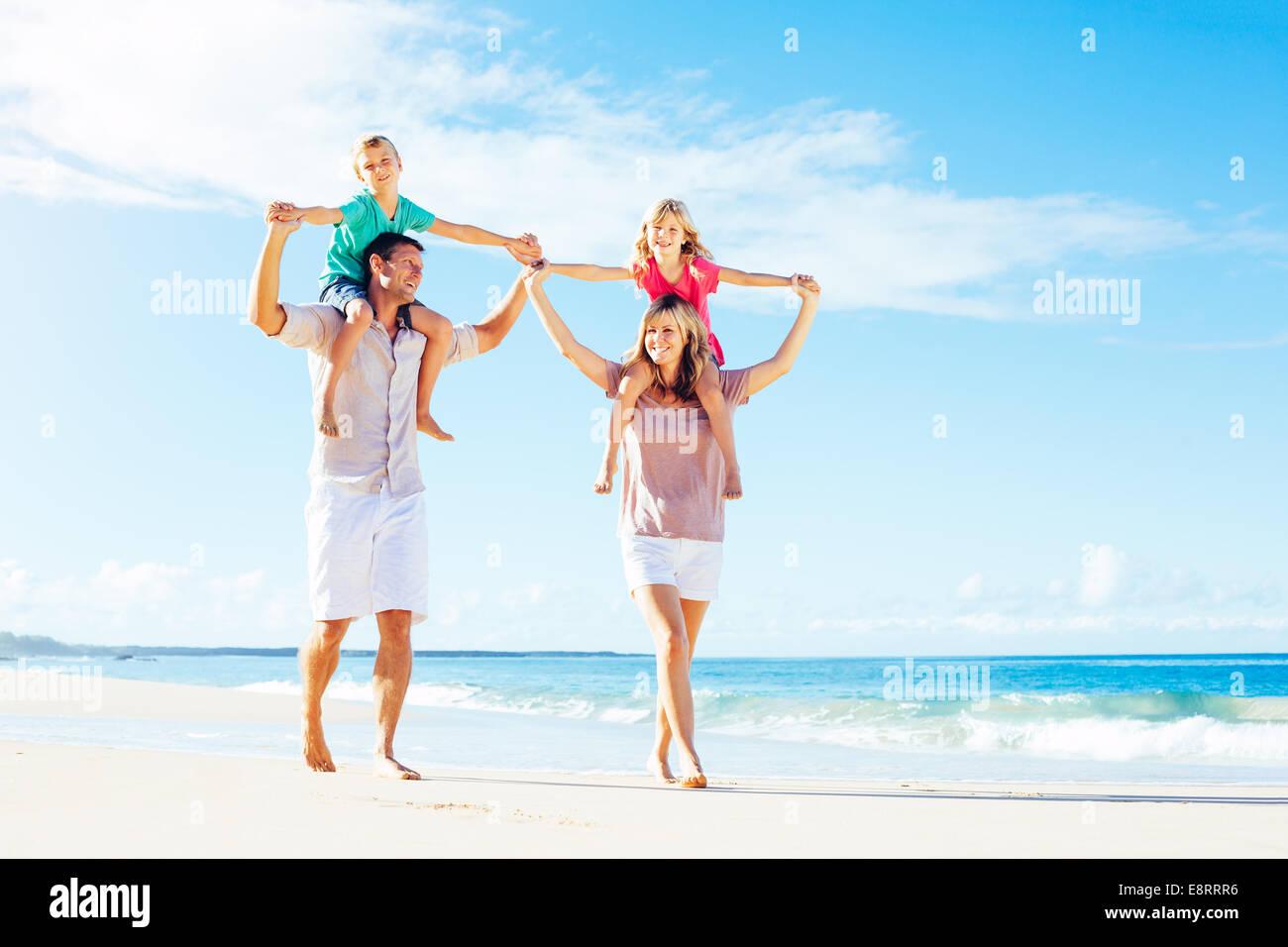 Foto di famiglia felice avendo divertimento sulla spiaggia. Lo stile di vita di estate. Immagini Stock