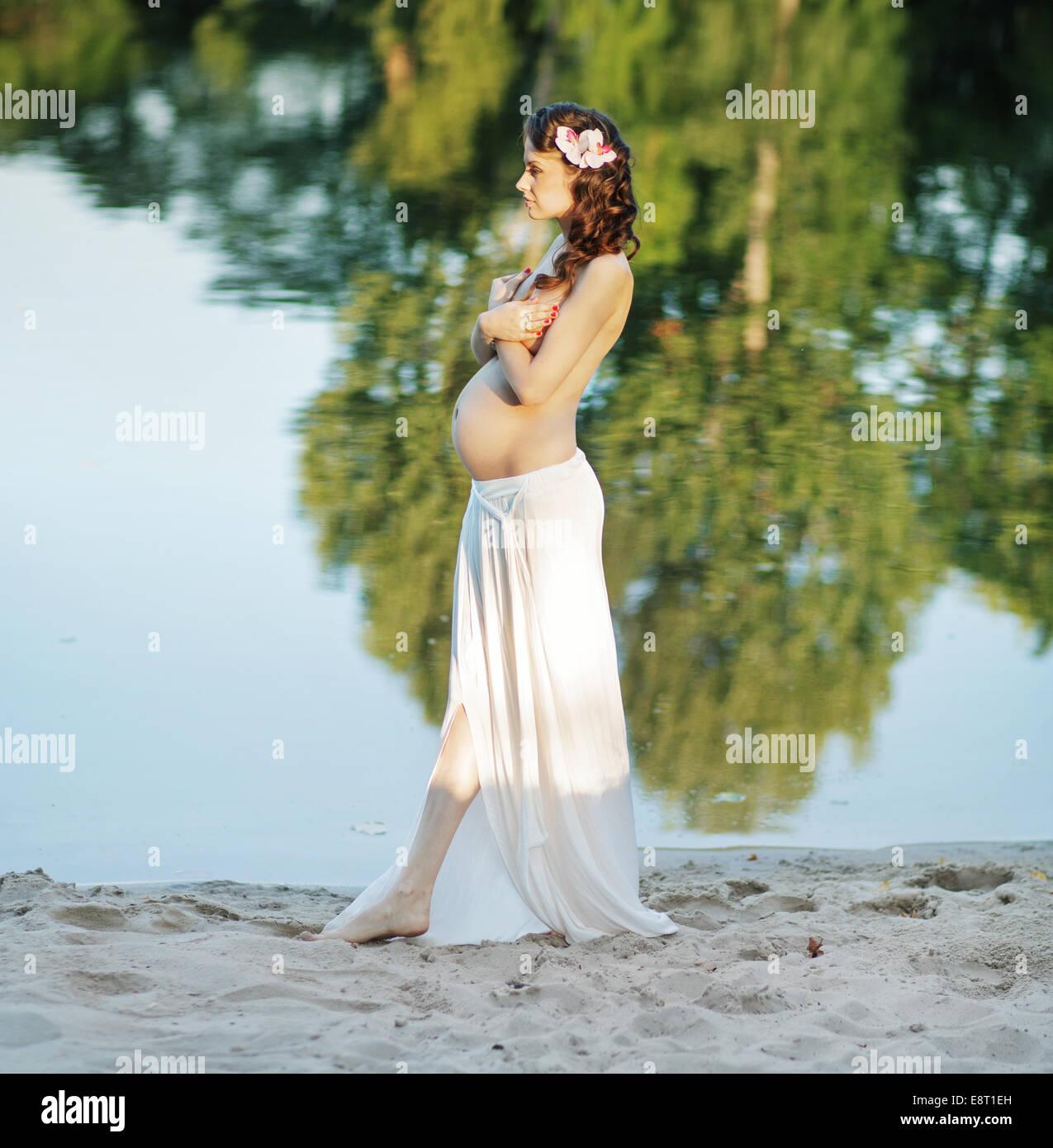 Donna incinta di camminare sulla spiaggia Immagini Stock