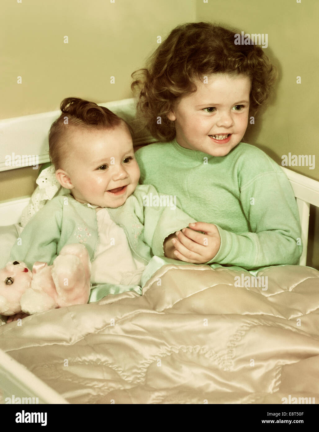 Negli anni quaranta anni cinquanta sorridente bambina e HAPPY BABY sorella  seduti insieme in un angolo 81ebd85ecf04