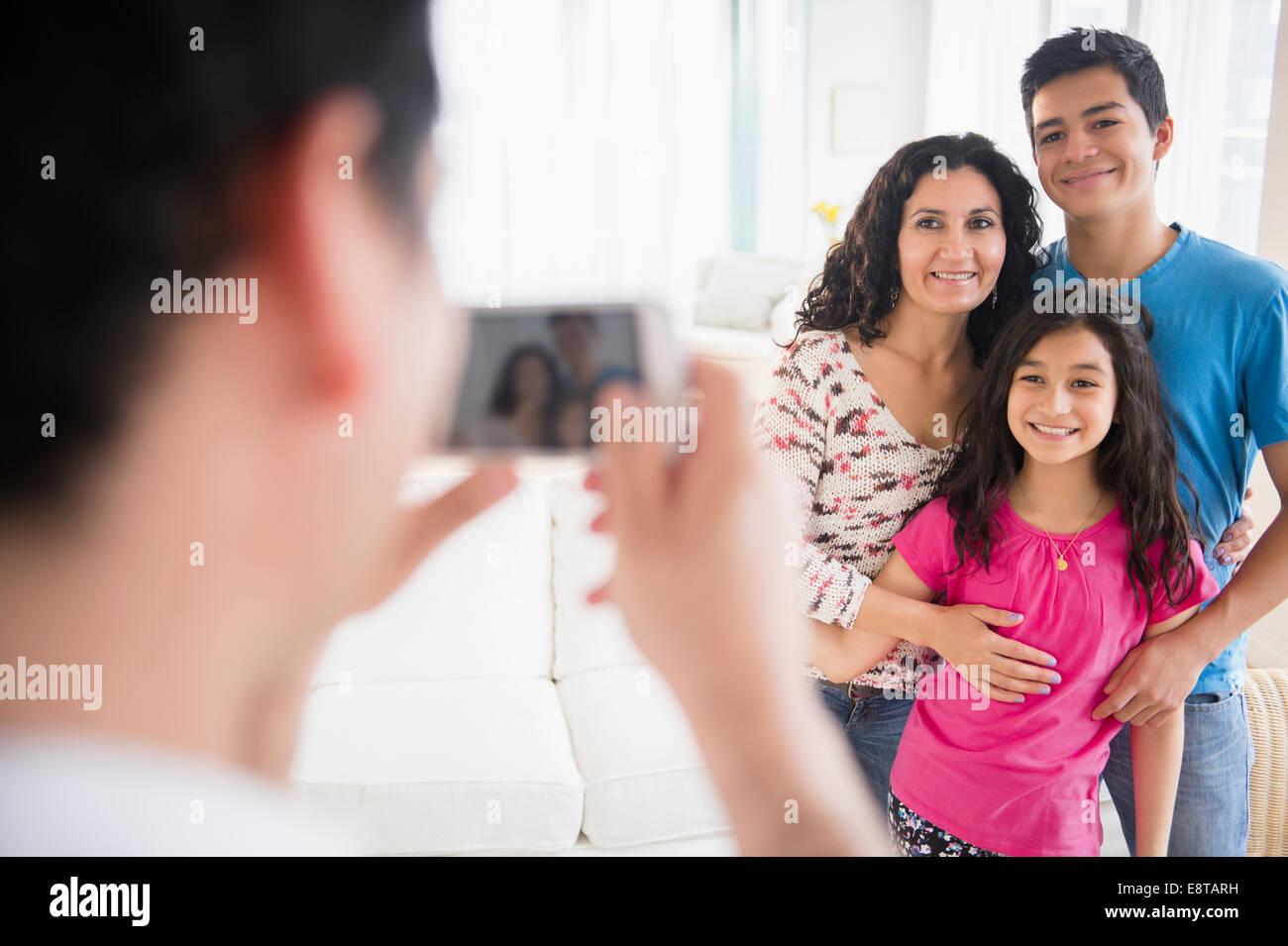 Famiglia di origine ispanica tenendo cellulare fotografia in salotto Foto Stock