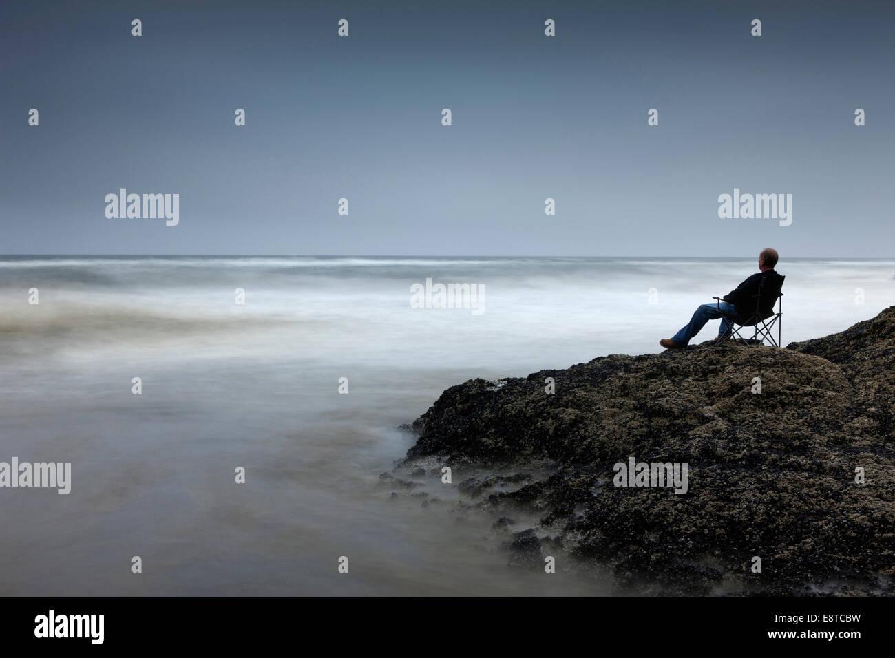 Uomo caucasico in cattedra si affaccia su onde sulla spiaggia rocciosa Immagini Stock