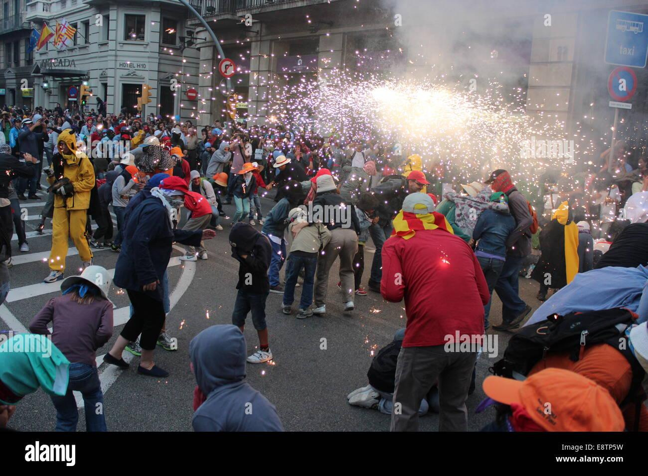 Barcellona, Spagna - 23 Settembre 2012: Revelers prendere la copertura da scintille e rumore forte durante il Correfoc Immagini Stock