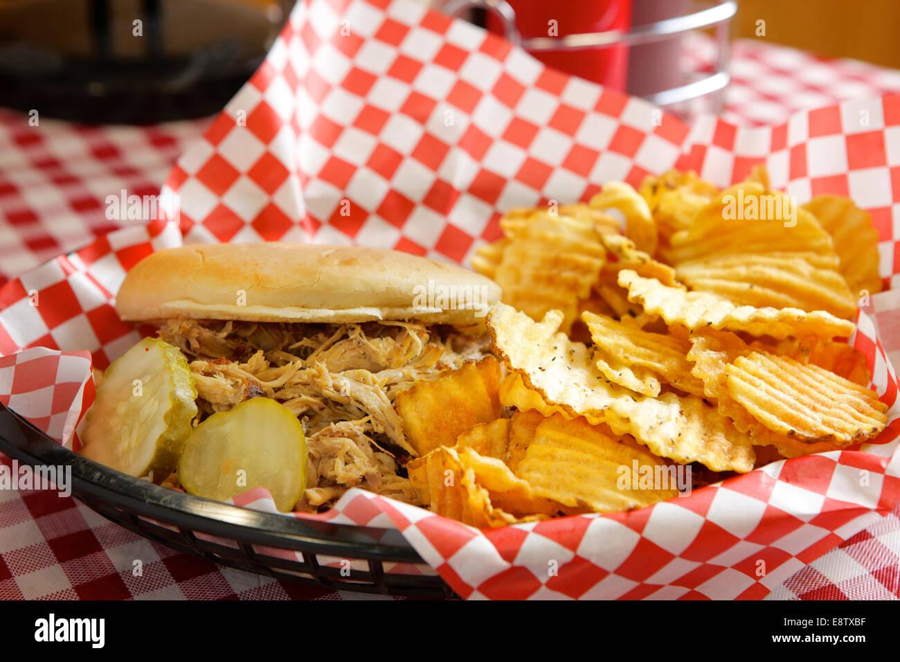 Tirato un sandwich di maiale con patate fritte e sottaceti Immagini Stock