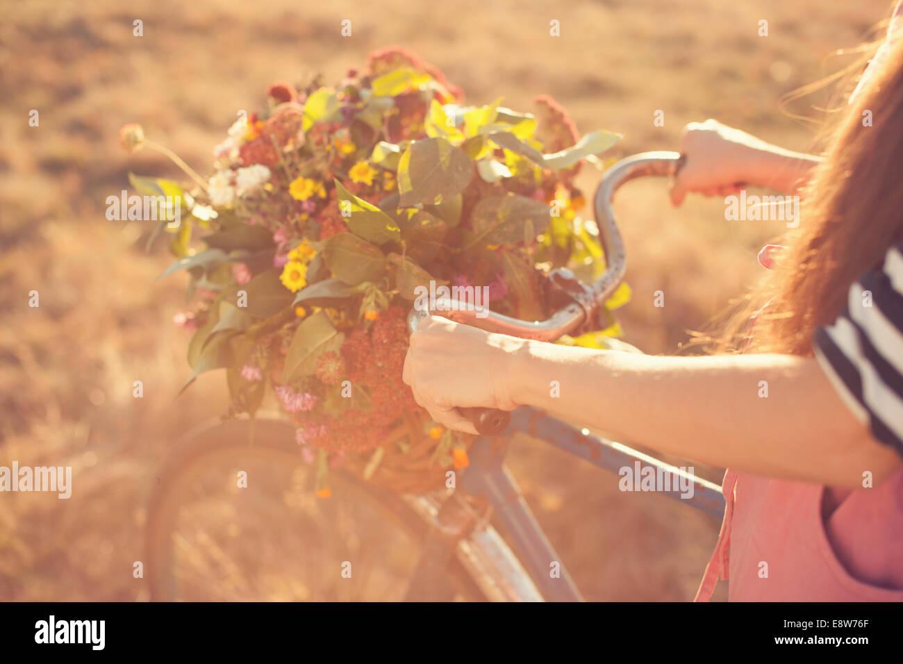 Bracci di ragazze in possesso di una vecchia moto manubrio con cestino dei fiori Immagini Stock
