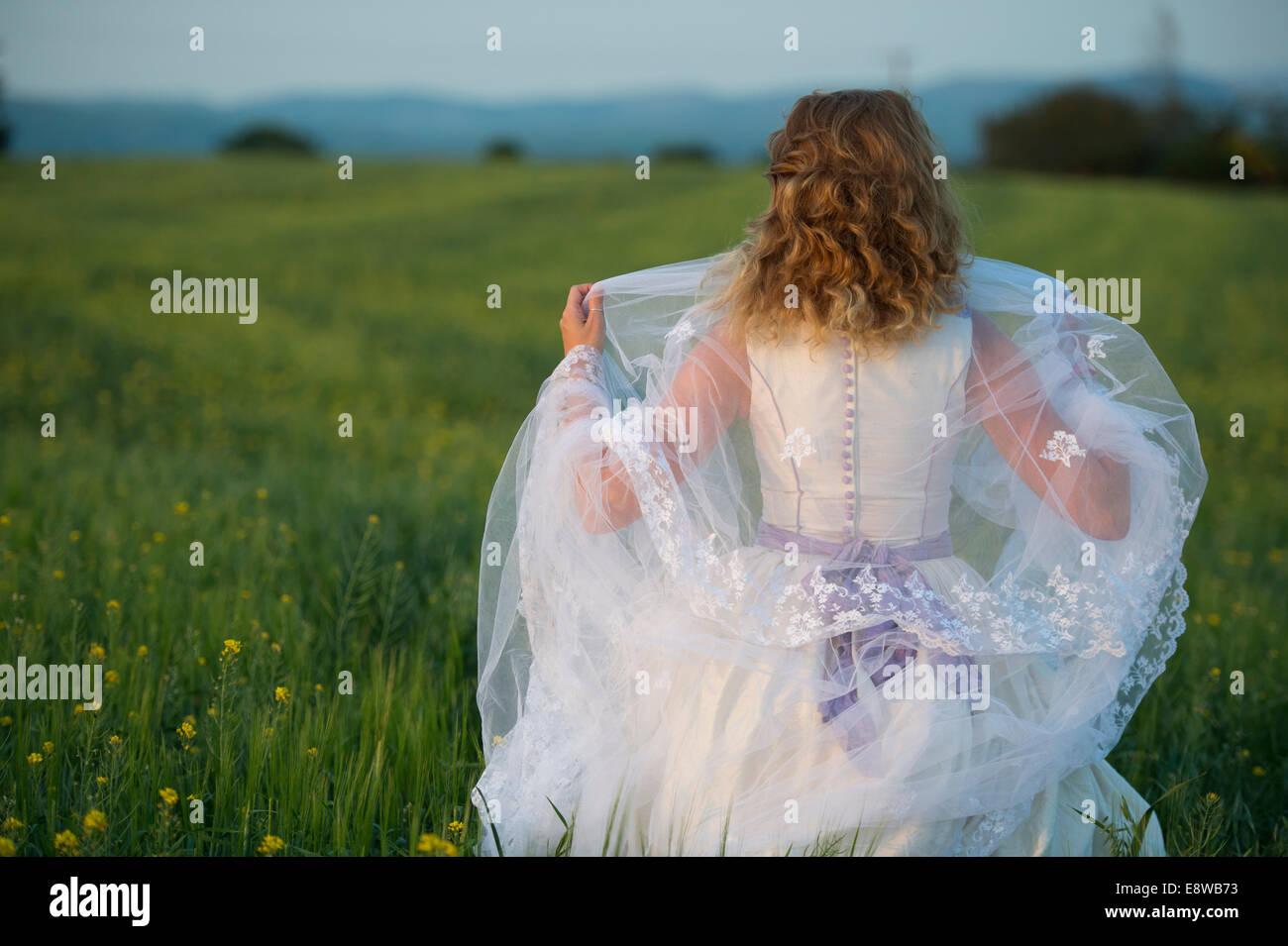 Il Runaway Sposa - una giovane donna ragazza in un abito da sposa in piedi in un campo di fiori gialli sera Immagini Stock