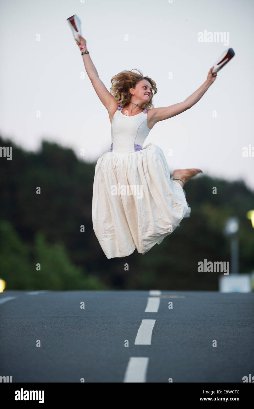 Il Runaway Sposa - una giovane donna ragazza in un abito da sposa salti di gioia per l'aria Immagini Stock