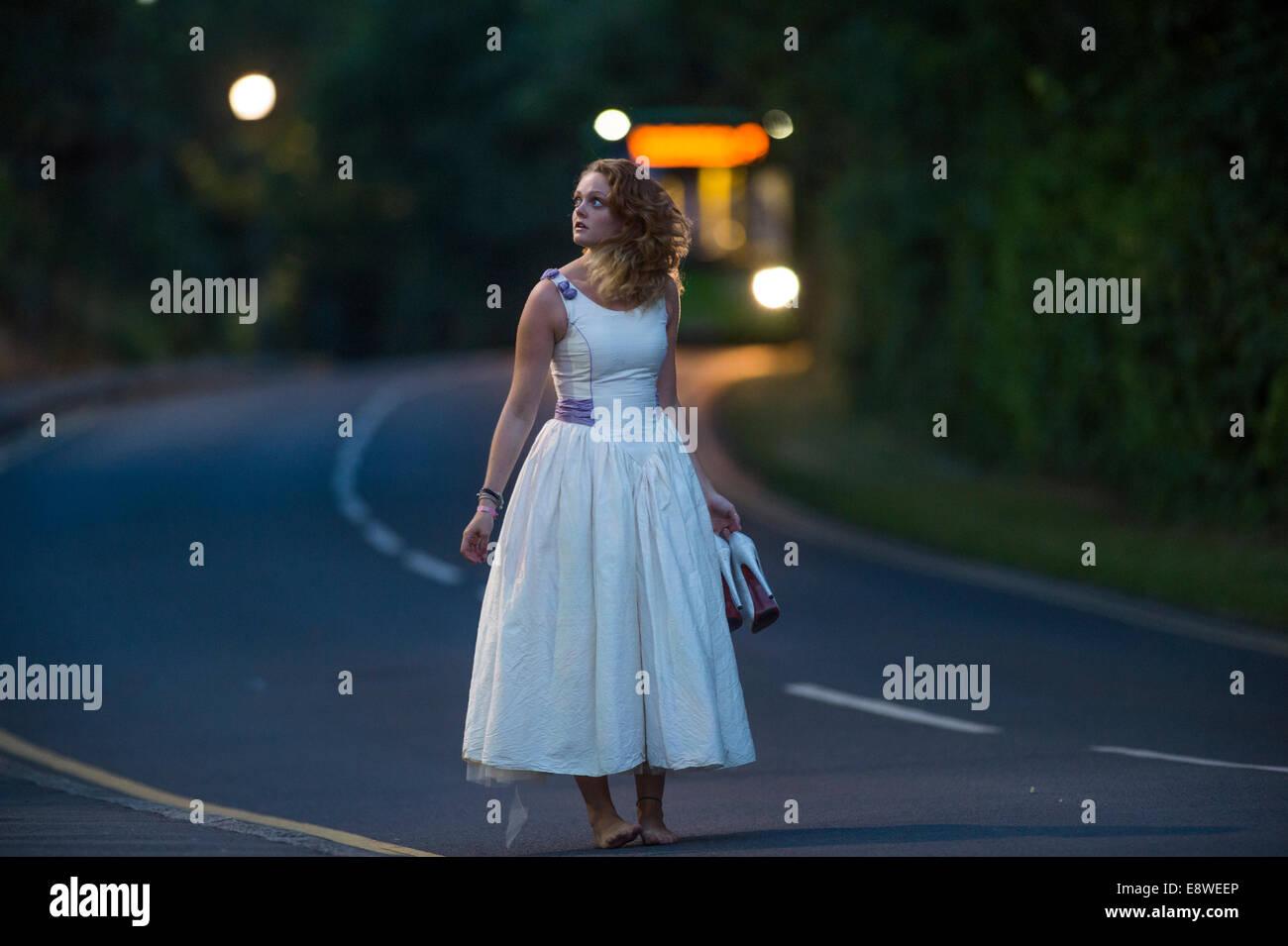 Il Runaway Sposa - una giovane donna ragazza in un abito da sposa camminare da solo a piedi nudi lungo una strada Immagini Stock