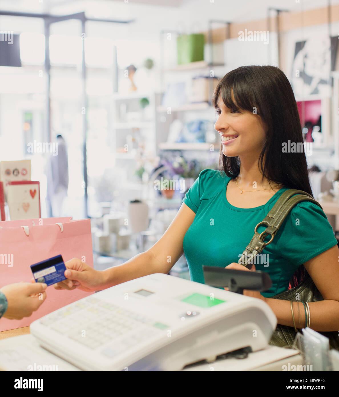 Donna pagando con carta di credito in negozio Immagini Stock