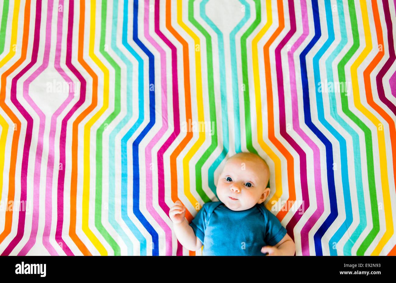 Baby recante sulla colorata tessuto geometrico, ad alto angolo di visione Immagini Stock