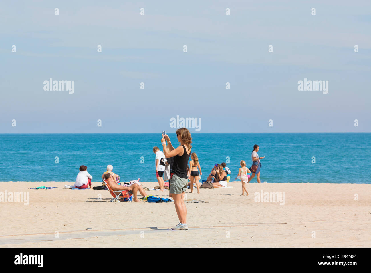 Donna sulla spiaggia con il telefono cellulare e scattare foto Immagini Stock