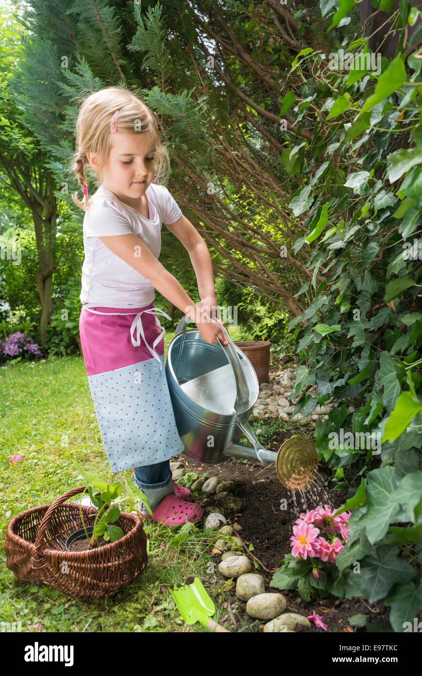 Ragazza giardinaggio, fiori di irrigazione con controllo Immagini Stock