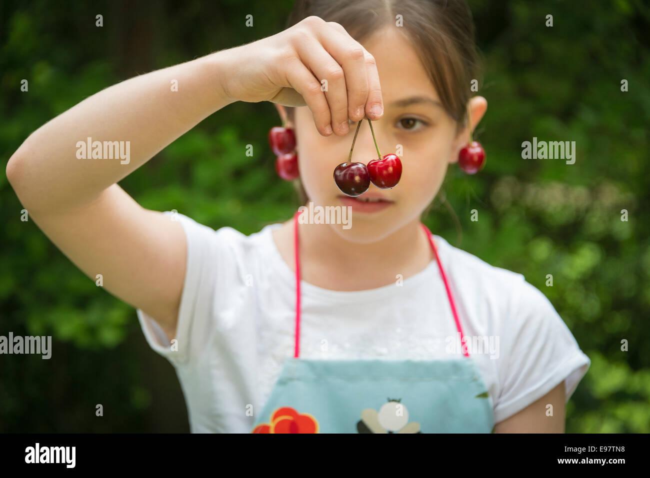 Ragazza con ciliegie penzolante dal suo orecchio Immagini Stock