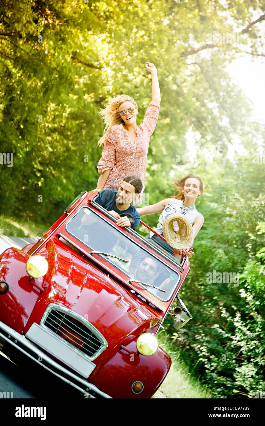 I giovani in rosso auto d'epoca, divertendosi Immagini Stock