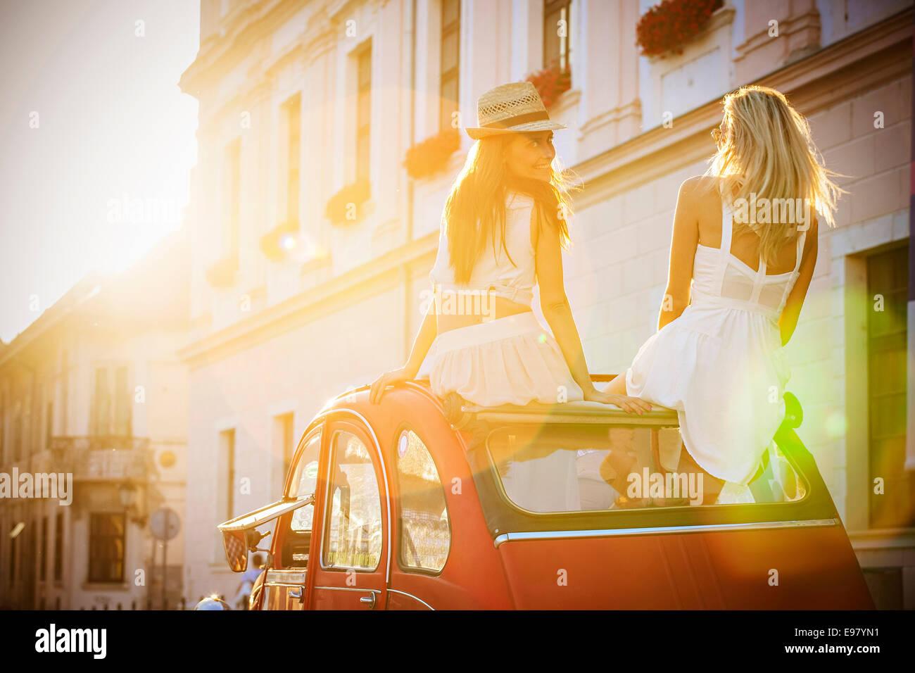 I giovani in vintage car guida attraverso la città Immagini Stock