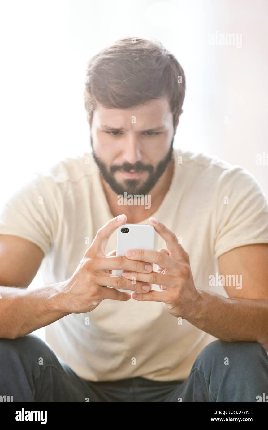 Maschio studente universitario utilizzando smart phone Immagini Stock