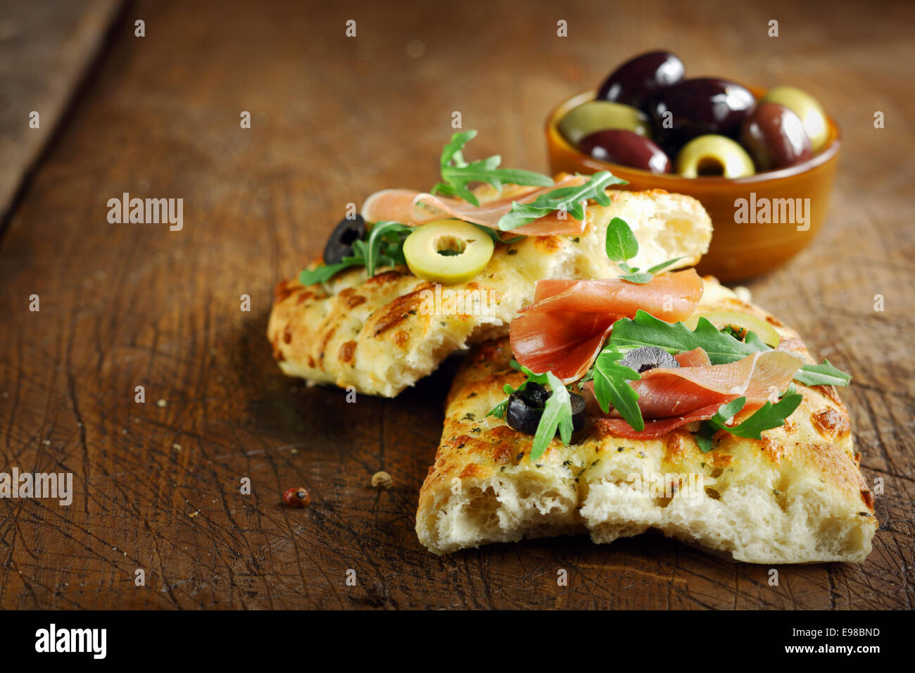 Prosciutto e rucola fresca sulla focaccia italiana guarnita con fette di olive giacente su una vecchia cucina in legno tavolo Foto Stock