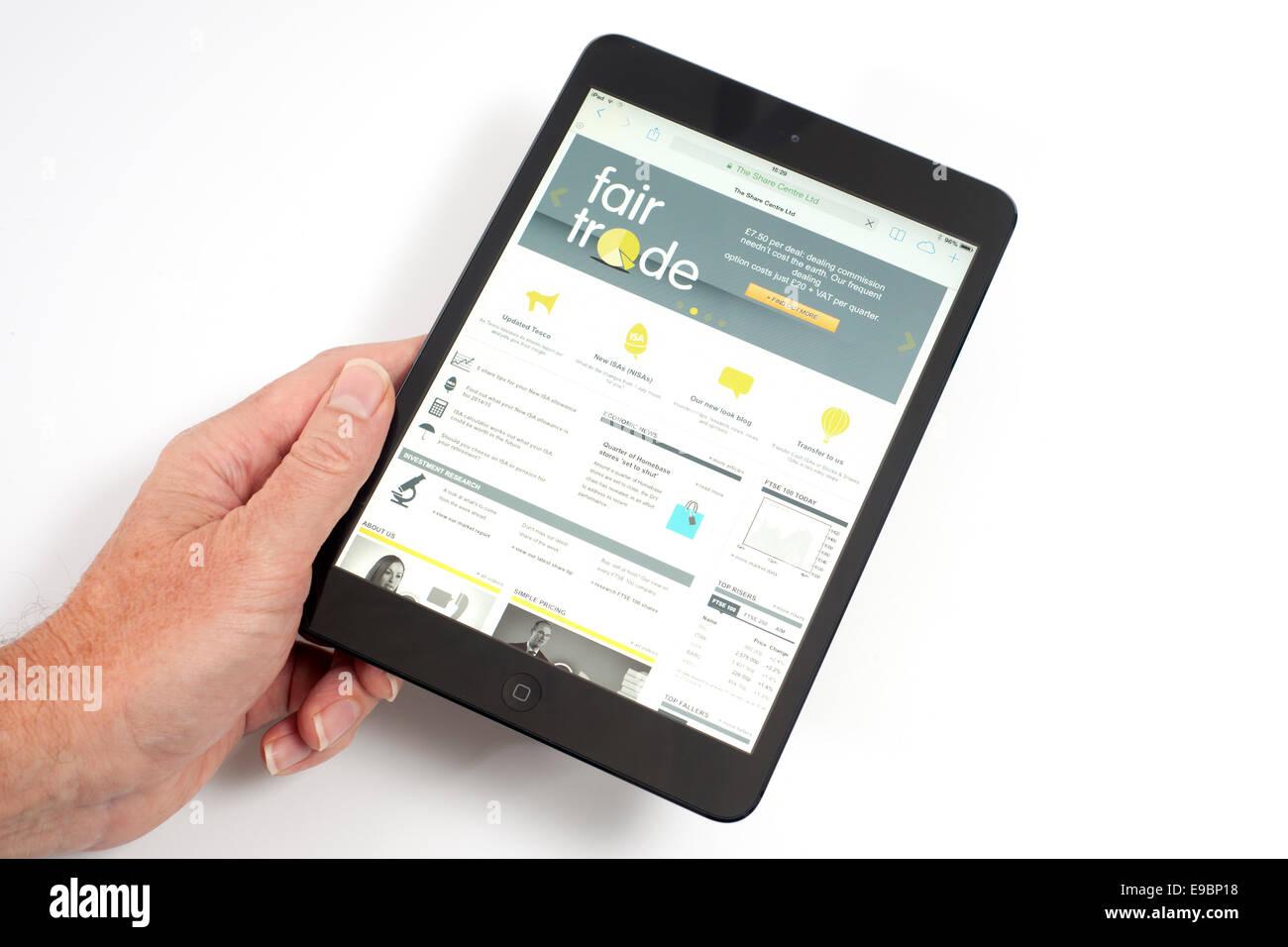 IPad mini con il commercio equo e solidale condividi trattare app sullo schermo Immagini Stock