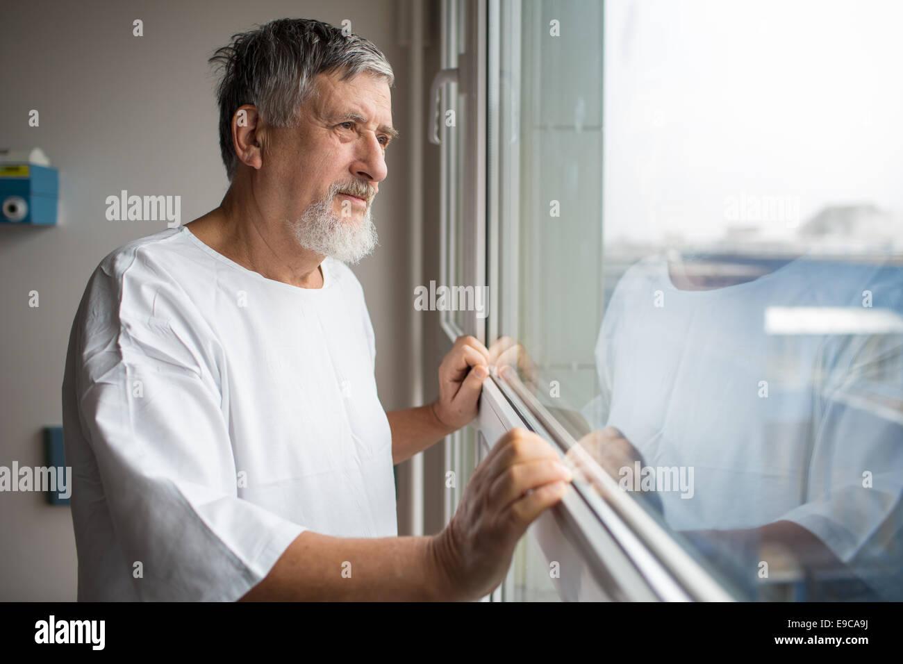 Paziente presso un ospedale, guardando da una finestra nella sua camera, facendo molto meglio dopo la chirurgia Immagini Stock