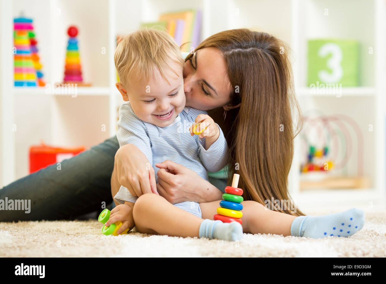 Felice la madre e il bambino figlio giocare indoor a casa Immagini Stock
