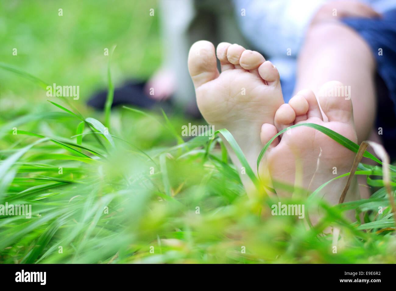 Little Boy con i piedi sul erba fresca Immagini Stock
