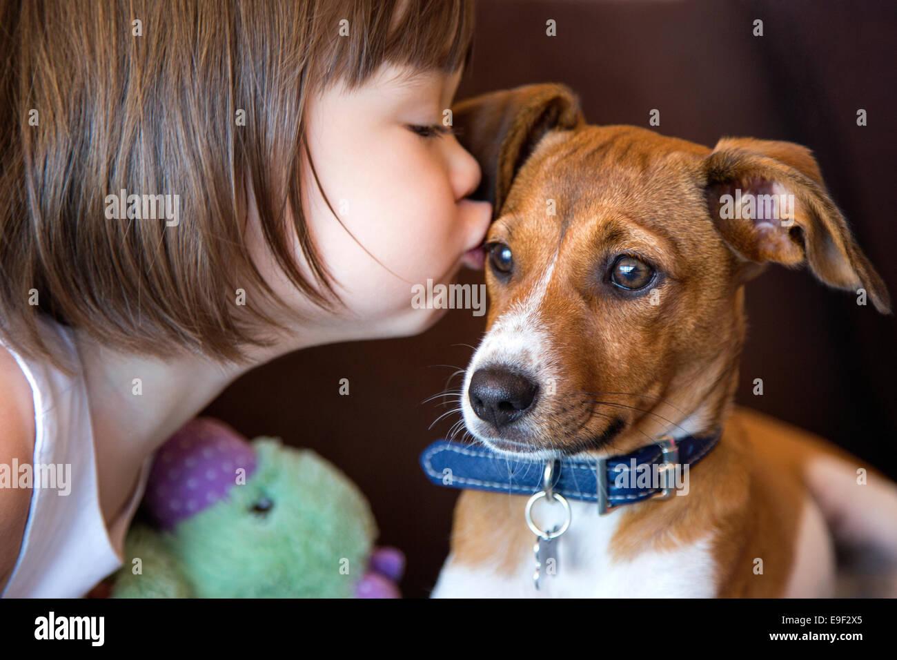 Il Toddler ragazza baciare il suo cucciolo di cane Immagini Stock