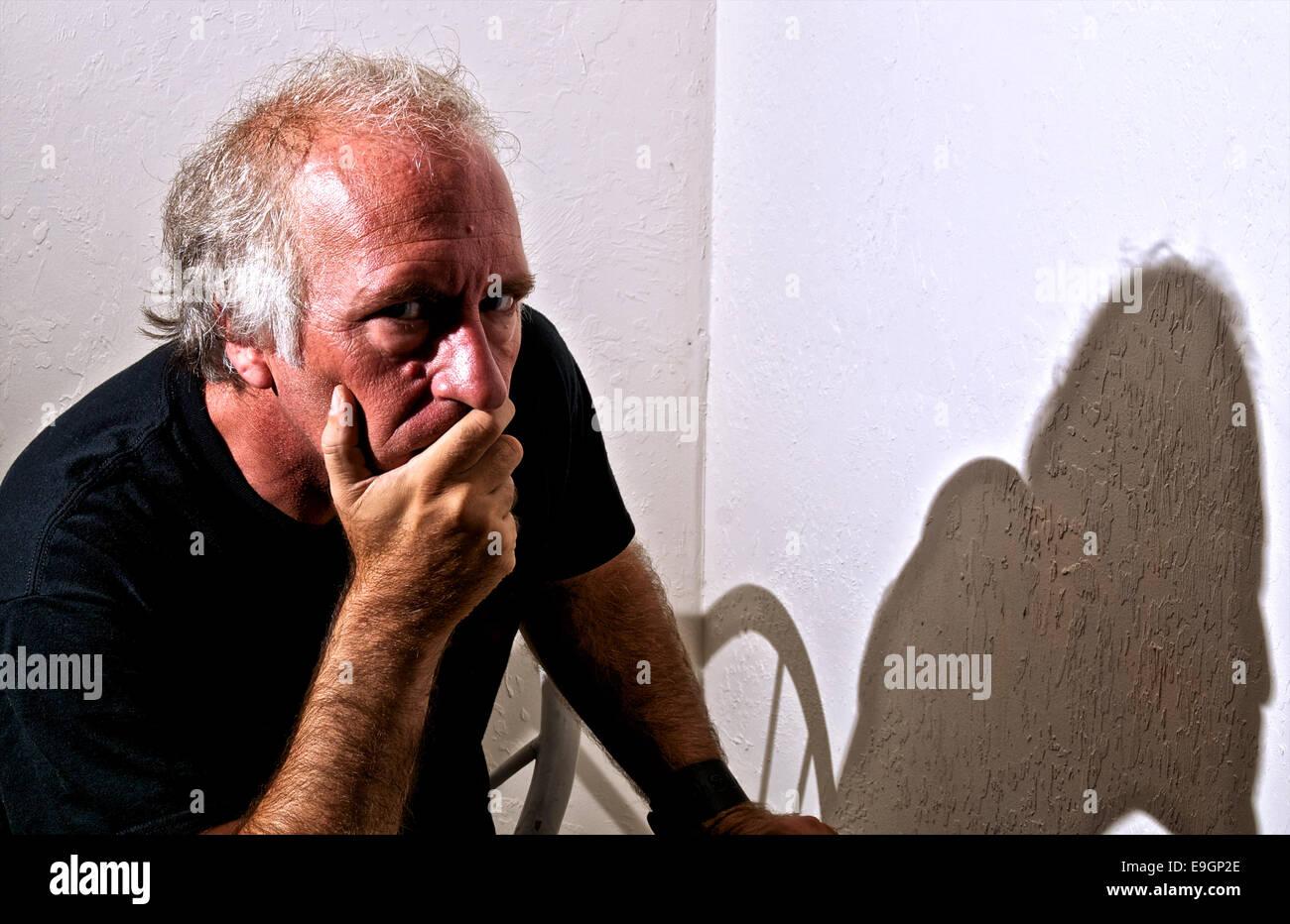 Un vecchio uomo bianco è di guardare direttamente viewer con un grave guardare negli occhi e che copre la bocca Immagini Stock