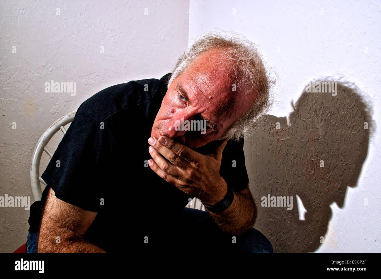 Un vecchio maschio bianco è seduto in un angolo su una sedia appoggiata in avanti e guardare lontano nel pensiero. Immagini Stock