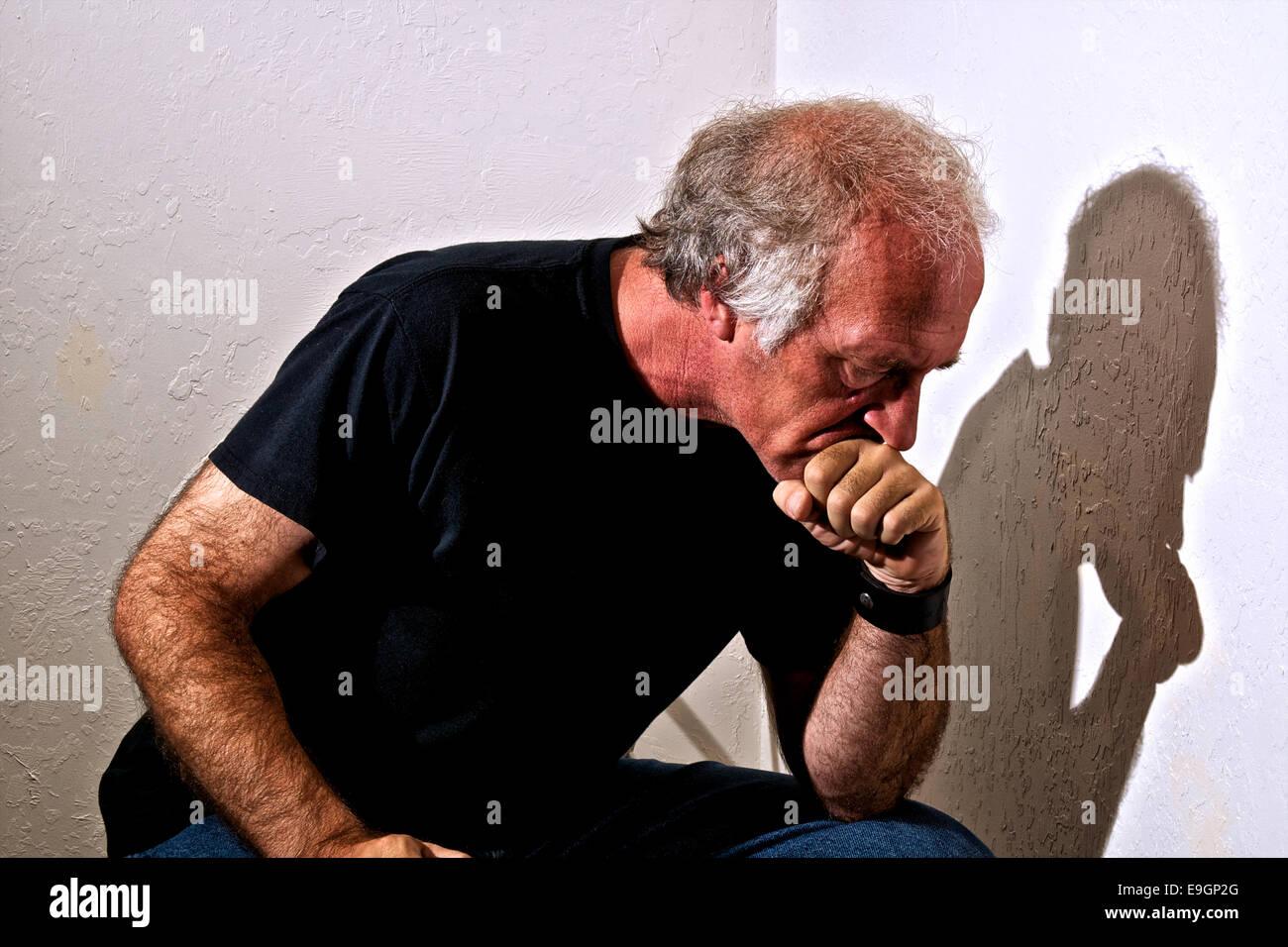 Un vecchio uomo premendo la bocca contro il pugno guardando giù nel pensiero, vista di profilo. Immagini Stock