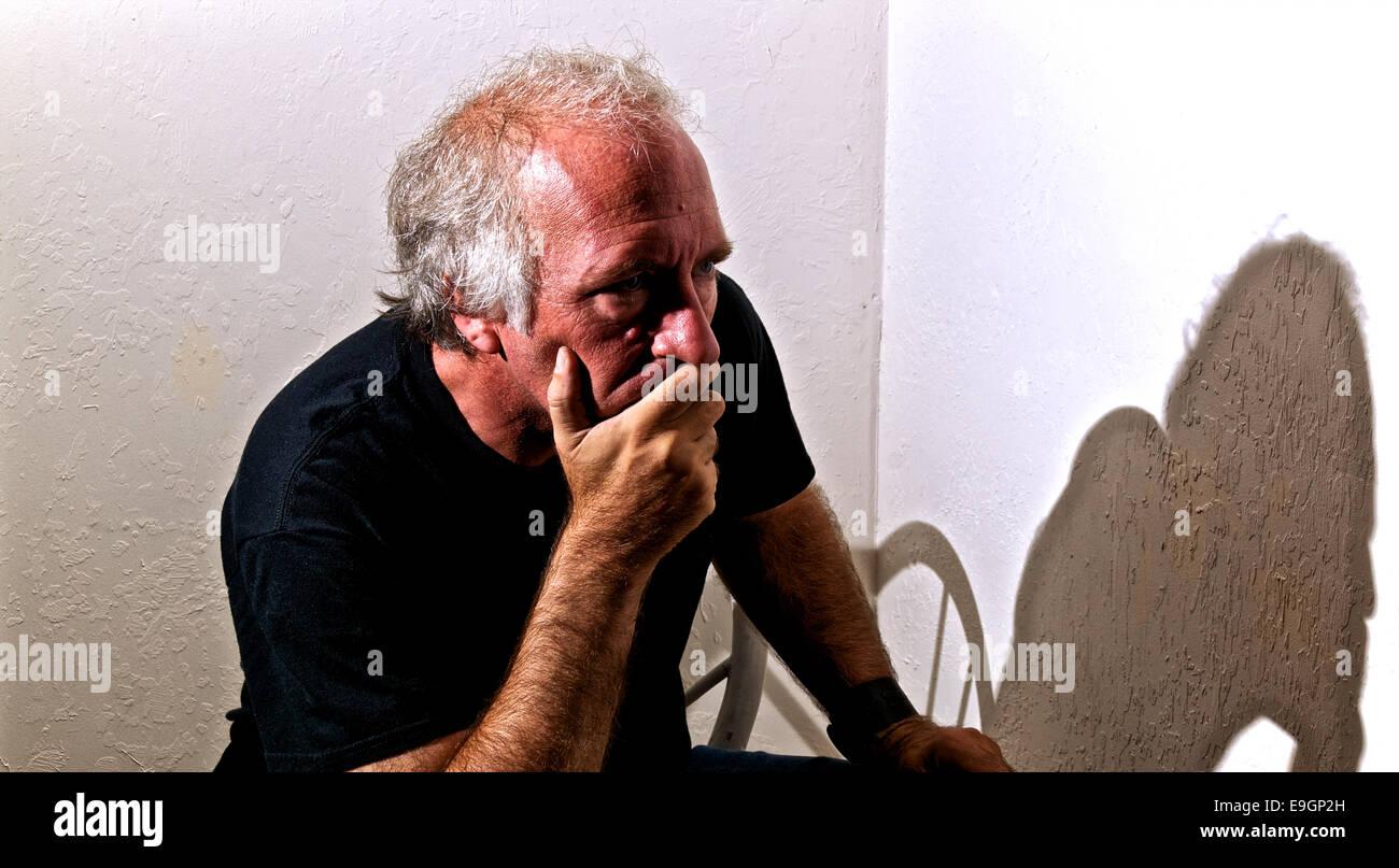Un vecchio uomo bianco è alla ricerca di distanza con una occhiata interessata sul suo volto e che copre la Immagini Stock
