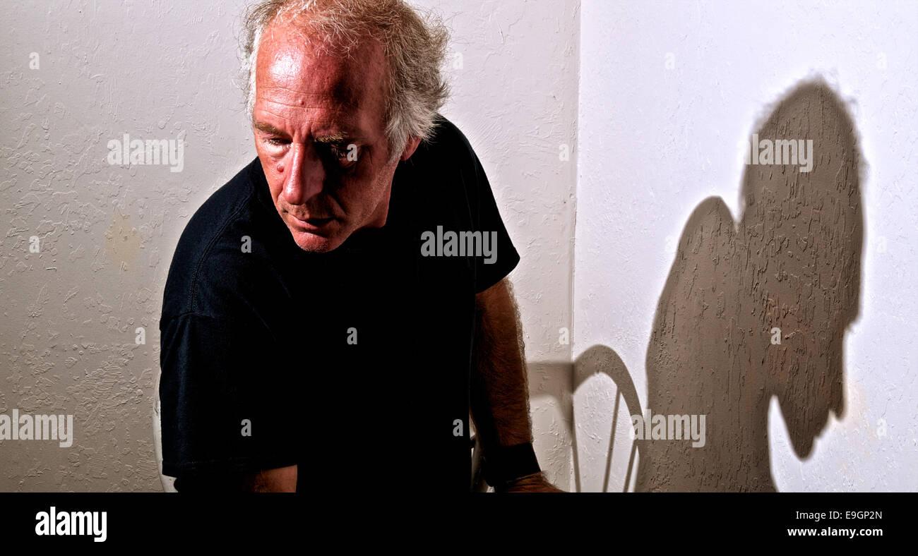 Un vecchio uomo bianco seduto in un angolo che guarda lontano con ombra. Immagini Stock