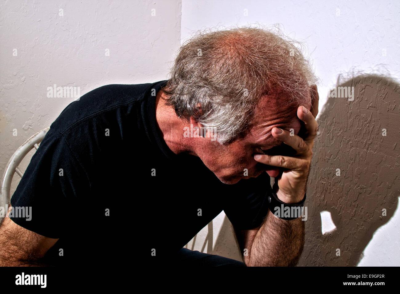 Ritratto di un distressed vecchio uomo bianco tenendo la testa seduto in un angolo della sala bianca. Immagini Stock