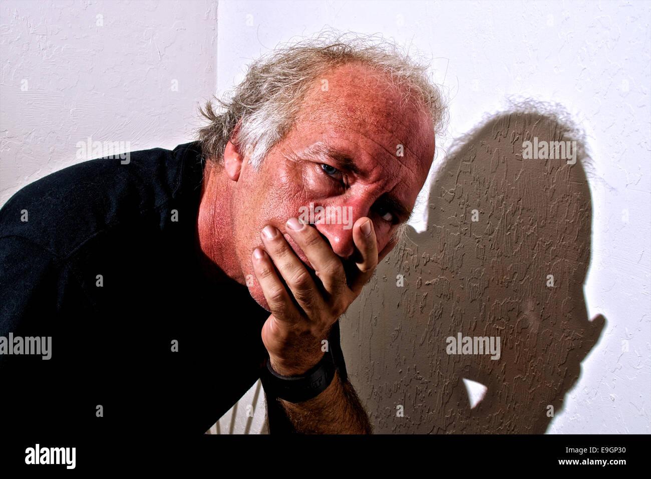 Un vecchio uomo bianco è di guardare direttamente viewer con un occhiata interessata ai suoi occhi e che copre Immagini Stock